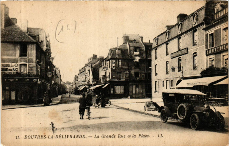 Carte postale ancienne Douvres-La-Delivrande - La Grande Rue et la Place à Douvres-la-Délivrande
